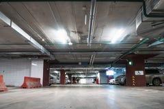 Interior subterrâneo iluminado da garagem de estacionamento do carro sob a alameda moderna com lotes dos veículos imagens de stock