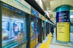Interior of a subway station and platform with subway commuters in Tokyo. TOKYO, JAPAN - NOVEMBER 28 2015:  Interior of a subway station and platform with subway Stock Photo