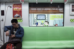 Interior of subway train carriage, Shanghai. A passenger relaxes in the carriage of a subway train in Shanghai underground transport system Royalty Free Stock Photography