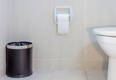Interior of toilet seat, paper and trashcan in hygiene restroom. Royalty Free Stock Photo
