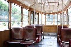 Interior of an tourism old vintage tram. Inside is empty, wooden red brown seats. Through the glass windows you can see the trees. Stock Image