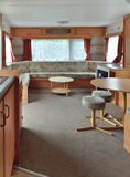 Interior of trailer in caravan park. Interior of living room in a caravan wagon or trailer, with chimney, curtains on windows, built-in sofas, tables and small Royalty Free Stock Images