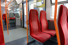 Interior of a train carriage. Empty red seats inside a commuter railway train carriage Stock Image