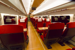 Interior of a train carriage. Looking straight down the central corridor between rows of plush red upholstered seats and tables for comfortable travel and Stock Photography