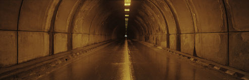 This is the interior of a tunnel. There is an orange glow from lights on the surrounding walls with a small light at the end of th Stock Image