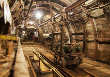 Interior of underground mine passage with rails, light and carriage. Mining industry Stock Image