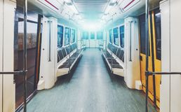 Interior of underground railway car. View of bright empty interior of modern subway train car while it is waiting on station with yellow doors opened Stock Photos