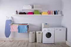 Interior Of Utility Room. With Washing Machine And Drying Clothes stock photo