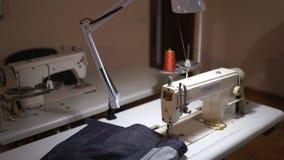 Interior vacío del taller del diseñador con las tablas y las máquinas de coser Estudio equipado de la adaptación de la moda dentr almacen de video