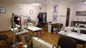 Interior vacío del taller del diseñador con las tablas y las máquinas de coser Estudio equipado de la adaptación de la moda dentr almacen de metraje de vídeo