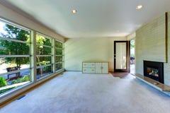 Interior vacío de la casa Sala de estar de la pared de cristal con la pared de ladrillo Imágenes de archivo libres de regalías