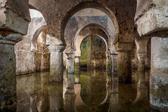 Interior view of the Arab cistern Caceres Spain, reflections of the arches in the water.  royalty free stock photography