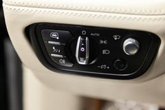 Interior view with headlight switch button and white leather control panel, black wooden trim and ventilation duct of luxury very royalty free stock photography