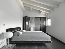 Interior view of a modern bedroom. In the mansard with black wood floor Royalty Free Stock Photos