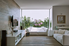 Interior view of a modern living room. Overlooking on the terrace with white fabric sofa and wood floor Stock Image