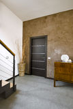 Interior view of a modern living room. With stiles  stone and wood door and staircase Royalty Free Stock Image