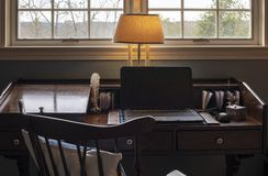 View of Home Office and Window. Interior view of an open laptop computer with blank screen. It is sitting on a wooden desk in fron of windows with a wooded view stock images