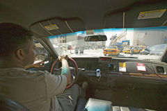 Interior view of taxi cab and driver steering through New York City, Manhattan streets, New York Stock Photo
