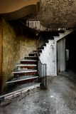Mountain Lodge - Abandoned Nevele Resort - Catskill Mountains, New York. An interior view of a traditional mountain lodge with a sweeping staircase at the Stock Image