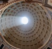 Interior view upward to the coffered concrete dome of Roman Pantheon with famous sunbeam and circular opening oculus in Royalty Free Stock Photo