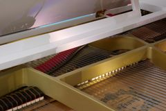 Close up view of the interior of a grand white piano with strings body royalty free stock photography