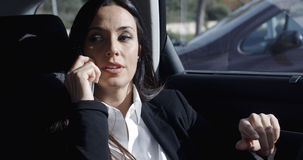 Interior view of woman on phone in limousine Royalty Free Stock Photos