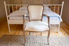 Interior of vintage bedroom. Bed and retro chair. Stock Photos
