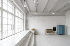 Interior with vintage furniture, light studio with old bench and blue case. Spacious studio with a high ceiling and a. Big window for photo shooting. Natural Royalty Free Stock Image