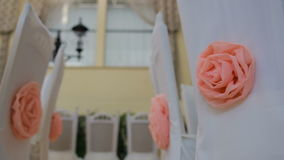Interior of a wedding hall decoration ready for guests. Nice decor with pink roses on white chairs stock video