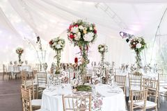 Interior of a wedding tent decoration ready for guests. Served round banquet table outdoor in marquee decorated flowers royalty free stock photos