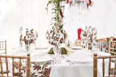 Interior of a wedding tent decoration ready for guests. Served round banquet table outdoor in marquee decorated flowers Royalty Free Stock Image