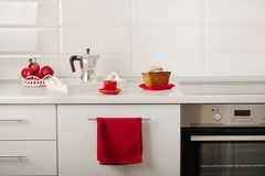 Interior white kitchen with kitchen tools and red crockery. Selective focus royalty free stock images