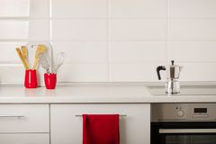 Interior white kitchen with kitchen tools and red crockery. Selective focus royalty free stock photos