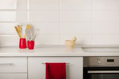 Interior white kitchen with kitchen tools and red crockery. Selective focus stock photo