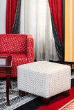 Interior with white pouffe and red sofa Stock Photos