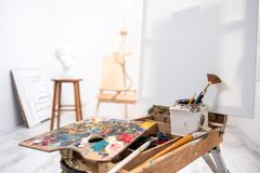 Interior of white studio of the artist, creative person. Easel, brushes, plaster head and figures. Attic, high ceilings. royalty free stock photo