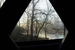 Interior window view from covered bridge on rural river and woods Stock Photography