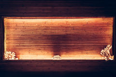 Interior wooden bamboo planks niche with warm orange light along the perimeter and copy space Royalty Free Stock Image