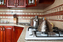 Interior of a wooden kitchen. Pan and kettle on the stove Royalty Free Stock Photos