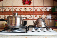 Interior of a wooden kitchen. Pan and kettle on the stove Stock Photos