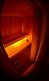 Interior of a Wooden Sauna. Interior of a wooden spa as viewed through a glass door with a fisheye lens Royalty Free Stock Photography