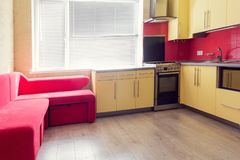 Yellow kitchen with cupboards, window, laminate and red soft cou Royalty Free Stock Images