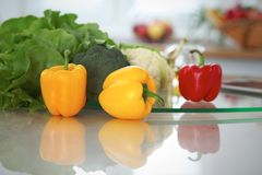 Interiores de la cocina Las muchas verduras y la otra comida en la tabla de cristal están listas para cocinado pronto Imagenes de archivo