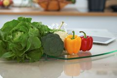 Interiores de la cocina Las muchas verduras y la otra comida en la tabla de cristal están listas para cocinado pronto Foto de archivo