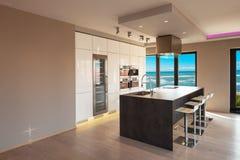 Interiores de un apartamento moderno, cocina con la opinión del mar Imagen de archivo libre de regalías