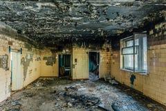 Interiores queimados após o fogo da construção industrial ou residencial Charred lavrou a parede Conceito das consequências do fo foto de stock royalty free