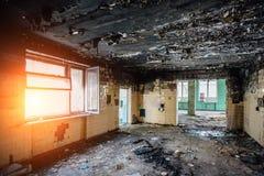 Interiores queimados após o fogo da construção industrial ou residencial Charred lavrou a parede Conceito das consequências do fo fotografia de stock royalty free