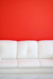 White Sofa against a Red Wall Stock Photography