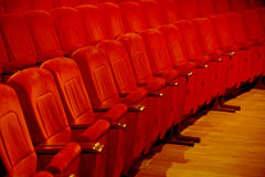 Interiors empty reddish cinema chairs seats in low-key indoors Stock Image