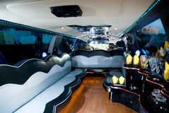 Interiors of a limousine. A closeup of the luxurious furnishing inside a modern limousine. A bar with empty glasses and black and gray leather seats have been Royalty Free Stock Photography